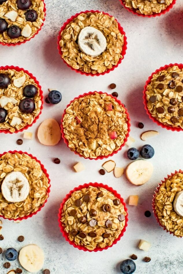 Muffin liners with baked oatmeal cups 4 ways. ingredients are surrounding them on the table like chocolate chips, blueberries, and apple chunks.