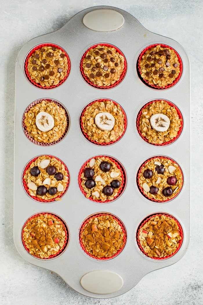 Muffin tin with baked oatmeal cups 4 ways in 4 rows.
