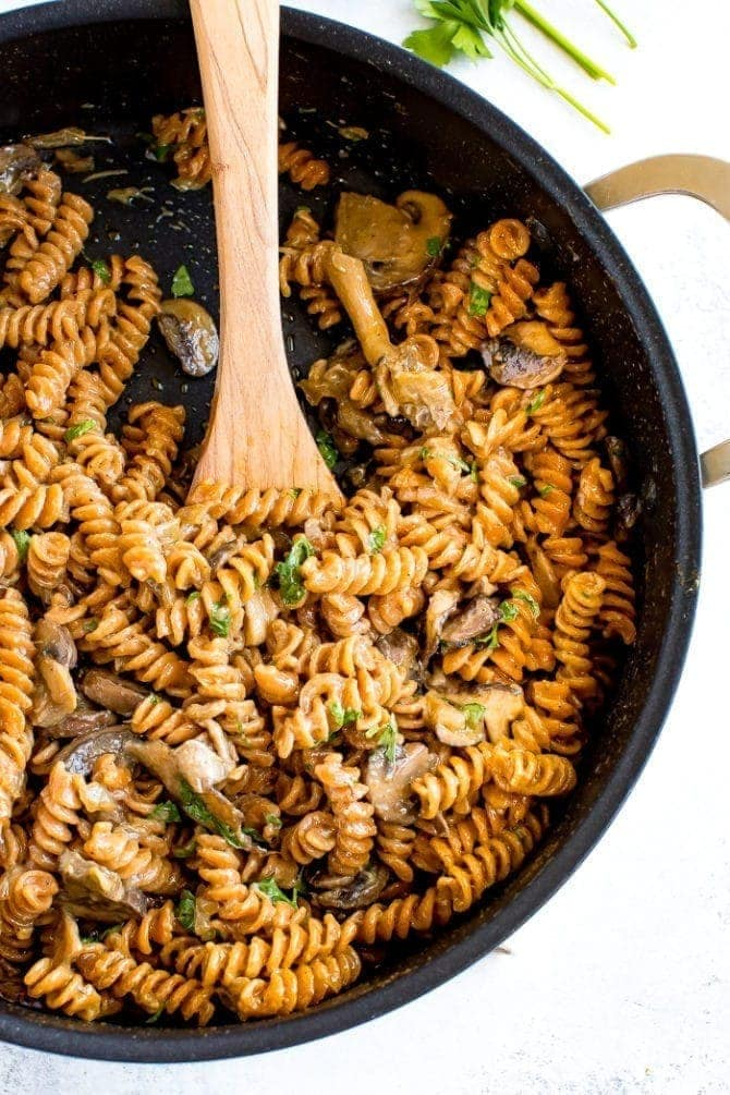 A skillet of healthy, protein-packed vegan mushroom stroganoff made with savory mushrooms, lentil pasta and a creamy coconut milk sauce.