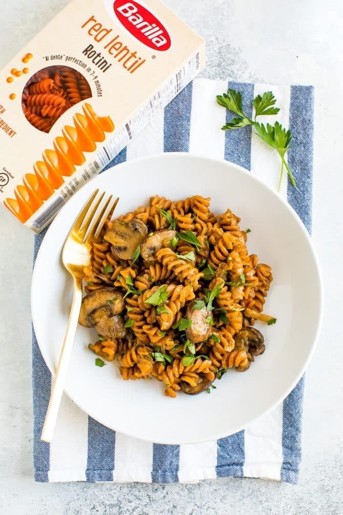 Vegan mushroom stroganoff on a plate next to a box of Barilla red lentil rotini.