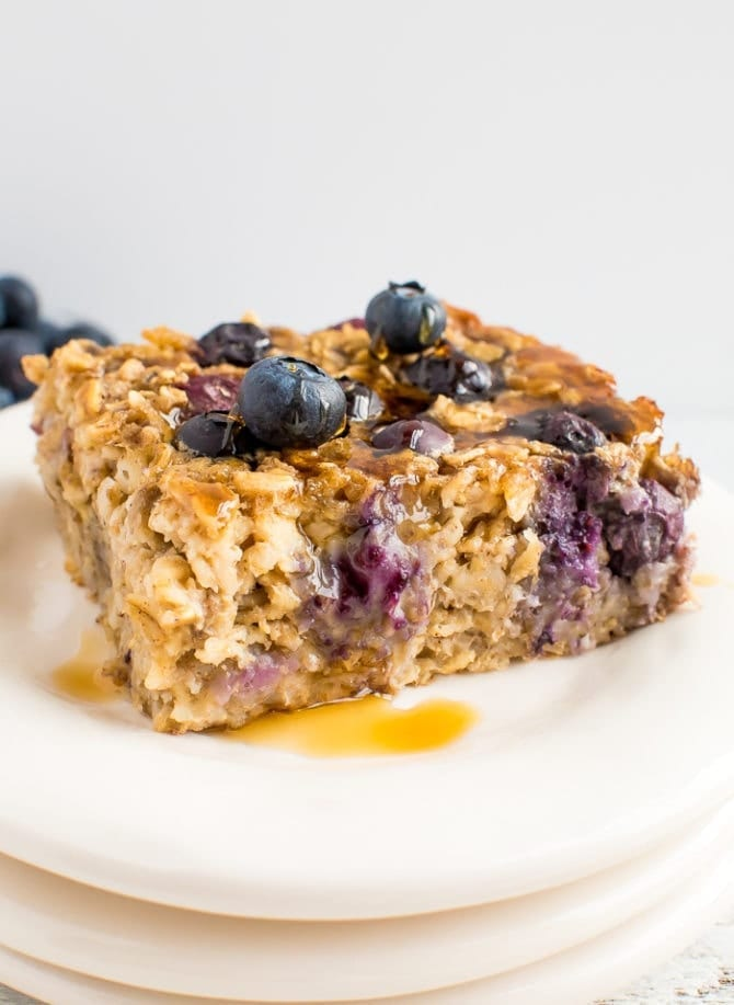 A slice of blueberry baked oatmeal topped with fresh blueberries and maple syrup.