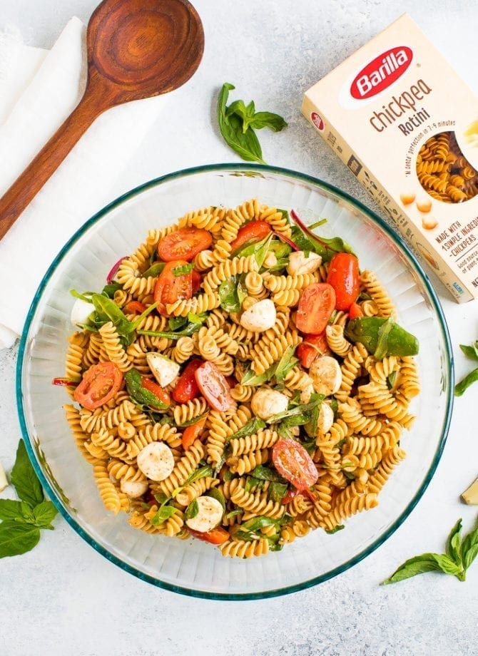 Serving bowl of gluten free caprese pasta salad with tomatoes, mozzarella, basil and a balsamic vinaigrette. Box of Barilla chickpea pasta is to the side.