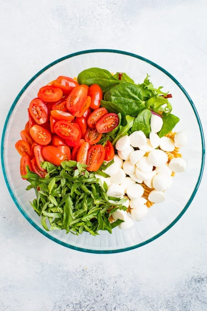Ingredients in a bowl for gluten free caprese pasta salad including chickpea pasta, cherry tomatoes, basil, fresh mozzarella and greens.