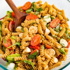 Serving bowl of gluten free caprese pasta salad with tomatoes, mozzarella, basil and a balsamic vinaigrette.