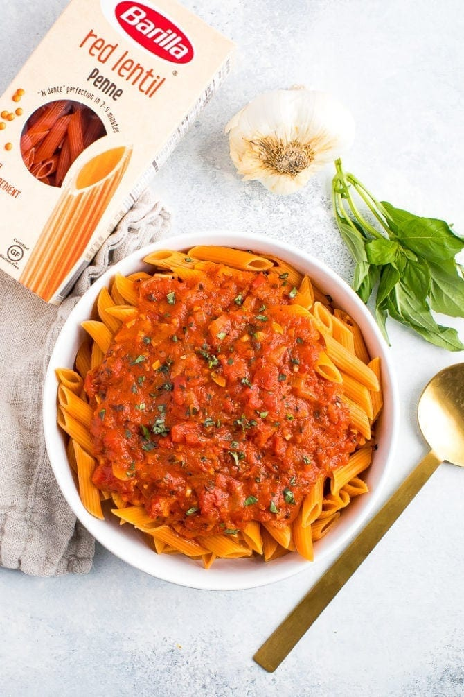Serving bowl of healthy, vegan and gluten free penne alla vodka next to a box of Barilla red lentil penne, garlic and fresh basil.