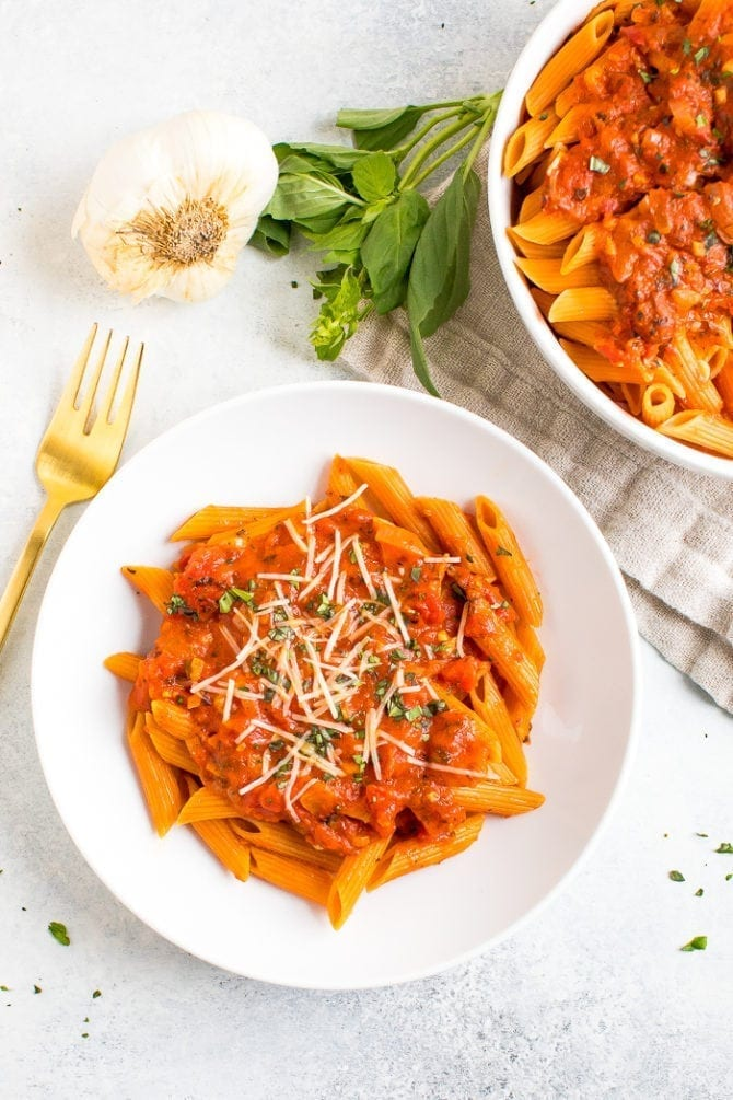 Healthy and vegan penne alla vodka on a plate next to garlic and fresh basil.