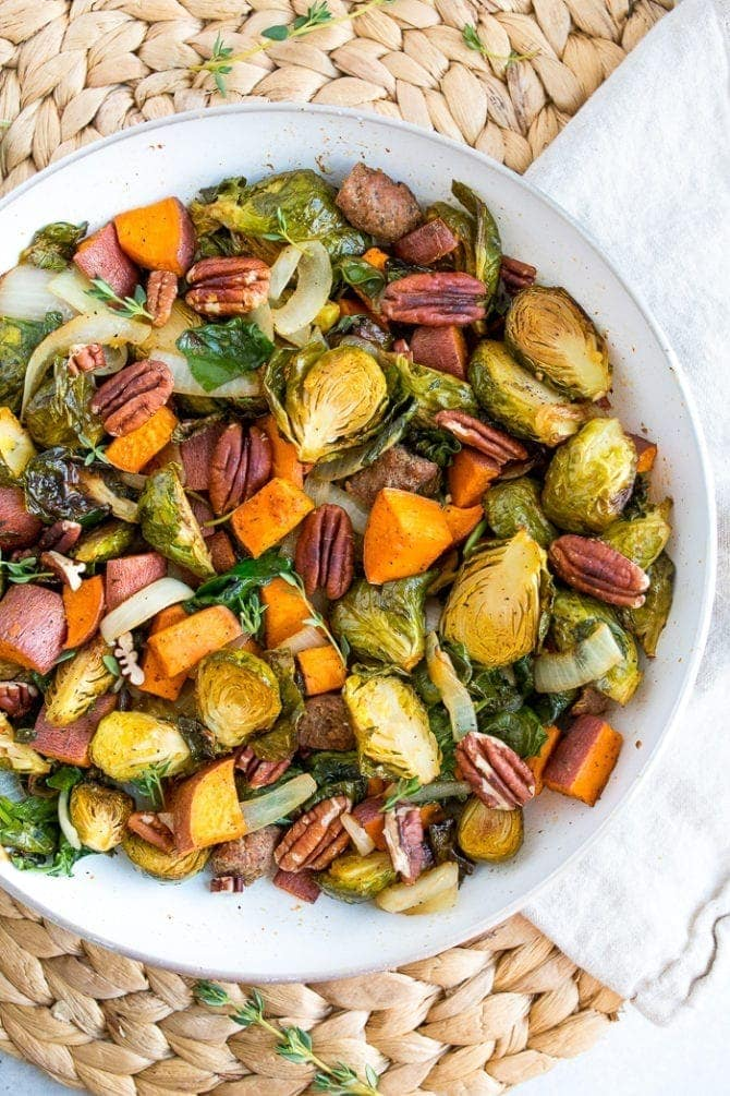 Breakfast hash on a plate with Brussels, pecans, sausage, and roasted sweet potatoes.