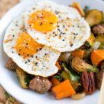 Sweet potato hash with brussel sprouts and pecans, topped with two over easy eggs, on a white plate.