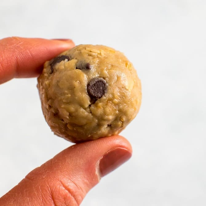 Hand holding a tahini chocolate chip protein ball.