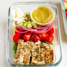 Glass meal prep container with grilled chicken tomatoes, pickled onions, cucumber, quinoa, greens, feta and a lemon vinaigrette.