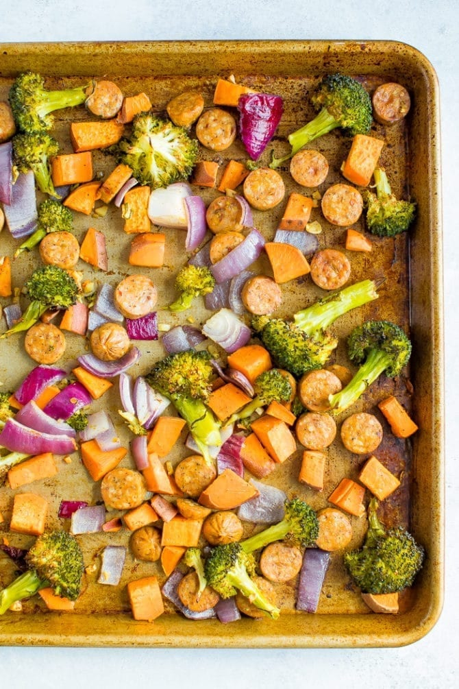 Sheet pan with roasted chicken sausage, red onion, broccoli, and sweet potato.