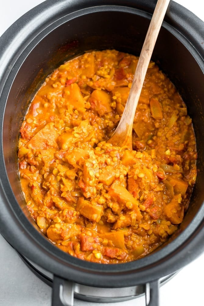 Vegetarian Slow Cooker Stew with Butternut Squash and Red Lentils in a slow cooker with a wooden spoon.