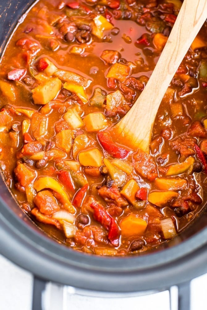 Vegetarian chili in a slow cooker made with sweet potatoes, black beans, peppers, and onions.