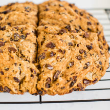 Irish soda bread made which whole wheat and raisins. Loaf is resting on a wire cooling rack.