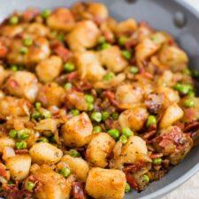 Skillet of Trader Joe's cauliflower gnocchi, sautéed with onions, peas, and turkey bacon.