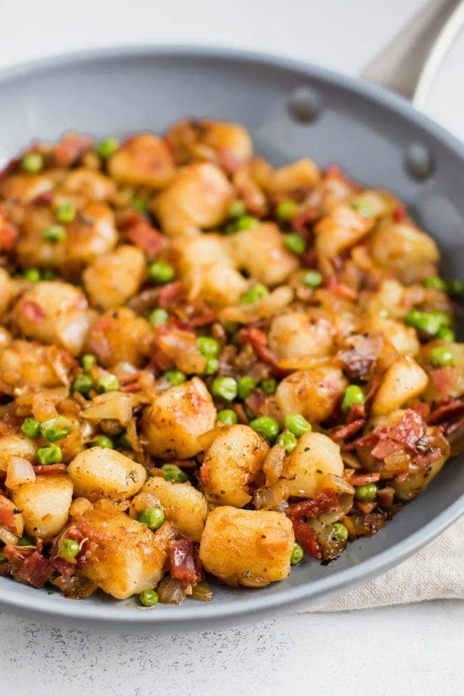 Skillet of Trader Joe's cauliflower gnocchi, sautéed with onions, peas, and turkey bacon.