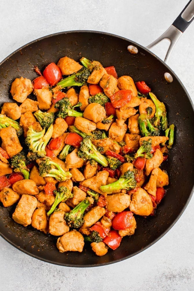 Healthy Kung Pao Chicken in a skillet with peppers and broccoli.