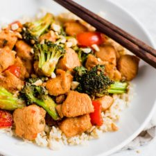 Kung pao chicken over rice with vegetables and peanuts on a plate with chopsticks.