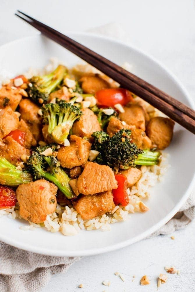 Healthy Kung Pao chicken with peppers, broccoli and chopped peanuts with rice in a bowl with chopsticks.