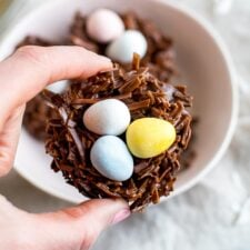 A hand holding a chocolate coconut flake Easter nest treat with Cadbury eggs in the nest.