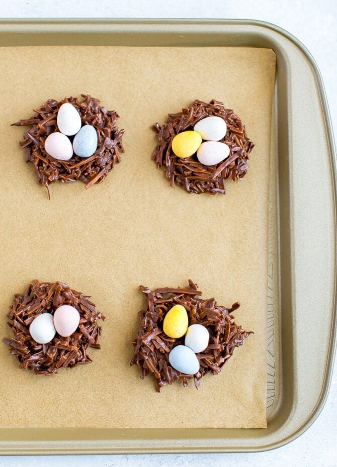 Chocolate coconut flake Easter nest treats with Cadbury eggs in the nest. Four nests on a cookie sheet lined with parchment paper.