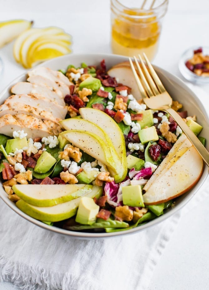 Salad topped with pears, grilled chicken, turkey bacon, cranberries, goat cheese, walnuts, and avocado.