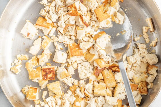 Sautéed crumbled tofu in a pan with a spoon.