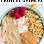 Hand holding a bowl of oatmeal topped with raspberries, granola, peanut butter and coconut.