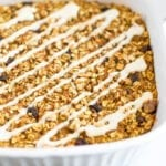 Carrot cake baked oatmeal in a baking dish drizzled with cream cheese frosting.