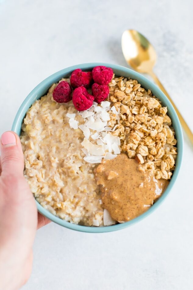 A bowl of egg white oatmeal with granola, freeze dried raspberries, coconut and almond butter in a blue bowl with a spoon.