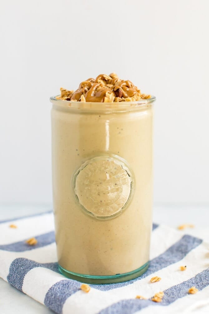 Cinnamon oatmeal cooke protein smoothie in a glass topped with granola and a peanut butter drizzle. Glass is on a striped napkin.