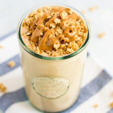 Cinnamon oatmeal cookie protein smoothie in a glass topped with granola and a peanut butter drizzle. Glass is on a striped napkin.
