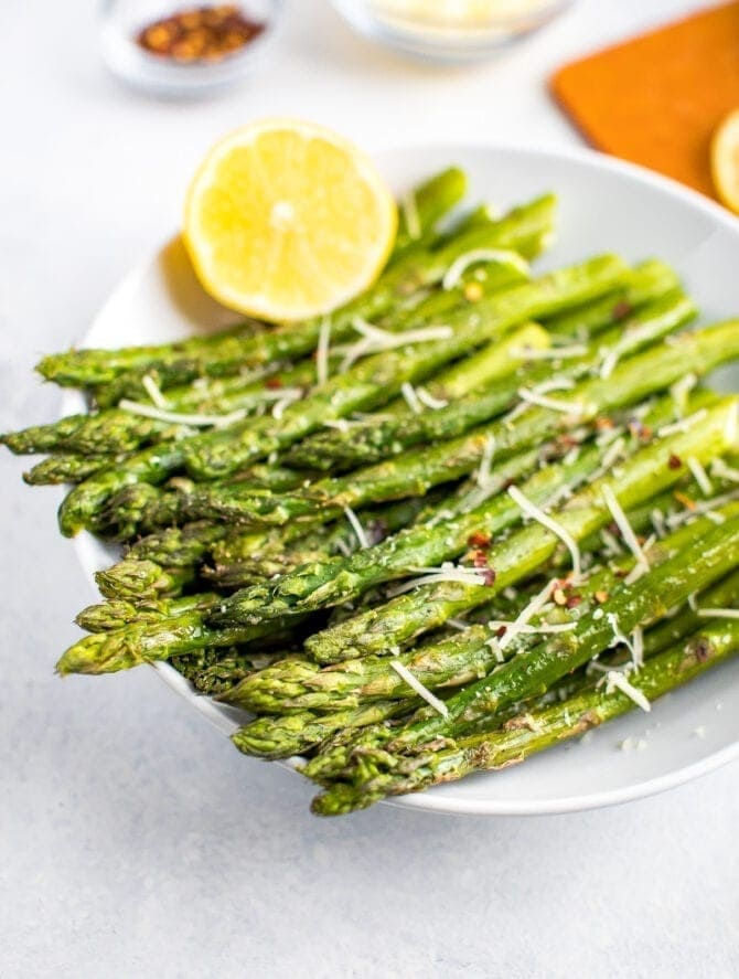 Roasted asparagus in a bowl, topped with parmesan, red pepper flakes, and fresh lemon.
