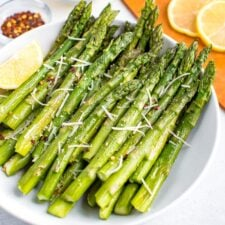Plate of roasted asparagus topped with parmesan, red pepper flakes, and a lemon wedge on the side. Beside the bowl are smaller bowls filled with red pepper, parmesan, and a cutting board with lemon slices.