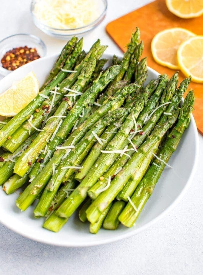 Roasted asparagus on a plate topped with red pepper flakes, parmesan and fresh lemon.