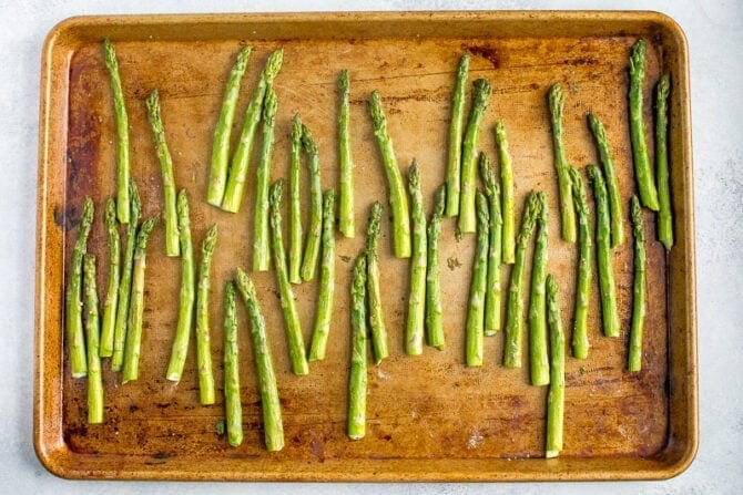 Sheet pan with asparagus, ready to be roasted in the oven.