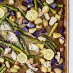 Sheet pain with purple potatoes, chicken, asparagus and lemon slices.