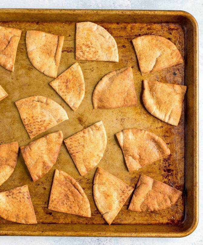 Baked pita chips on a baking sheet.