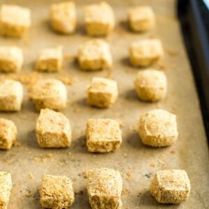 Cubes of tofu baked on a sheet pan lined with parchment paper, and coated in oat flour and nutritional yeast.