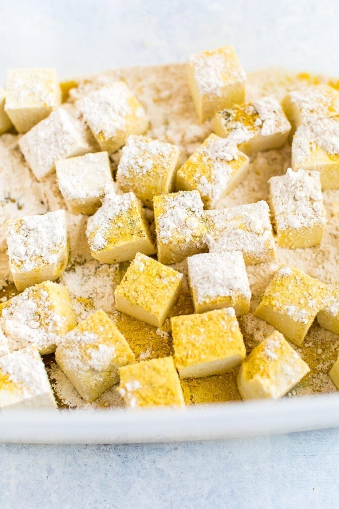 Cubes of tofu being tossed with spices, oat flour and nutritional yeast.