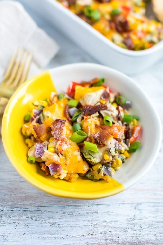 a bowl of chicken casserole made with corn, kale, cheese and bacon. topped with green onions.