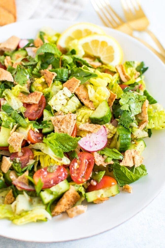 Plate of fattoush salad made with lettuce, herbs, tomato, cucumber, radishes and crumbled pita chips.