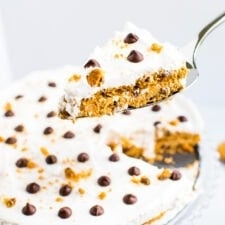 Spatula with a slice of chocolate chip cookie icebox cake, topped with whipped cream and chocolate chips and cookie crumbs. The icebox cake is in the background.