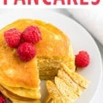 stack of coconut flour pancakes topped with raspberries and maple syrup