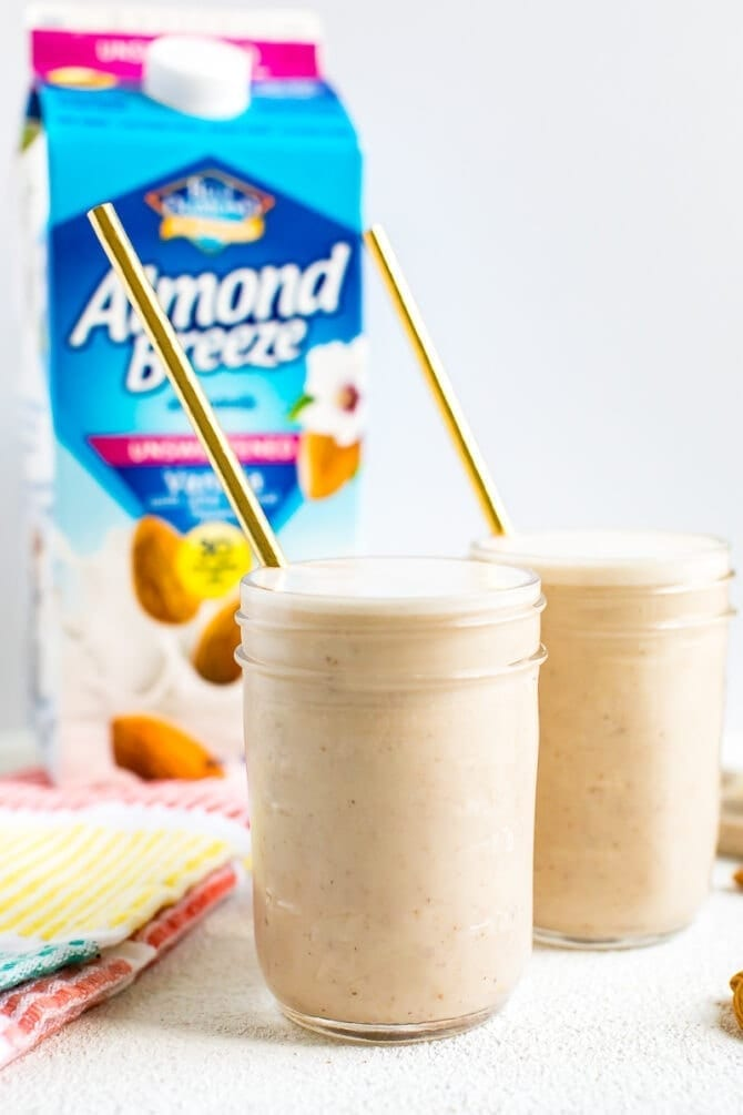 Two small mason jars with banana almond butter smoothie and straws. A carton on Blue Diamond almondmilk is behind the glasses.
