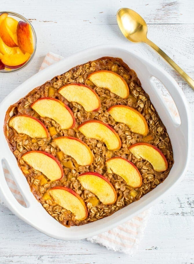 Baked oatmeal in a square dish and topped with peaches. A bowl of peach slices and a spoon are to the side.
