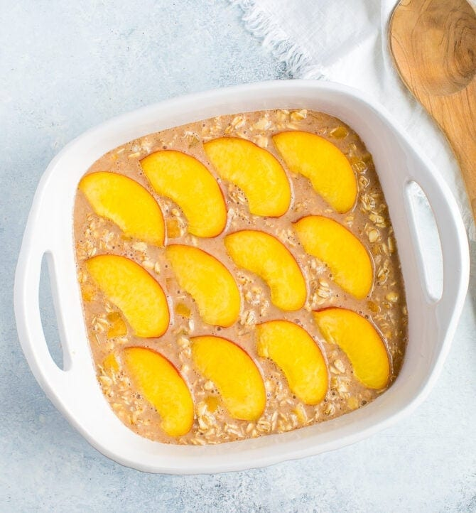 Baking dish with unbaked oatmeal topped with peach slices.