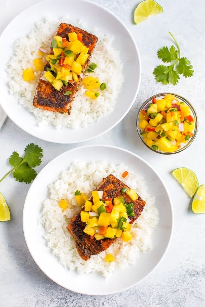 Two plates with rice, blacked salmon, and pineapple salsa.