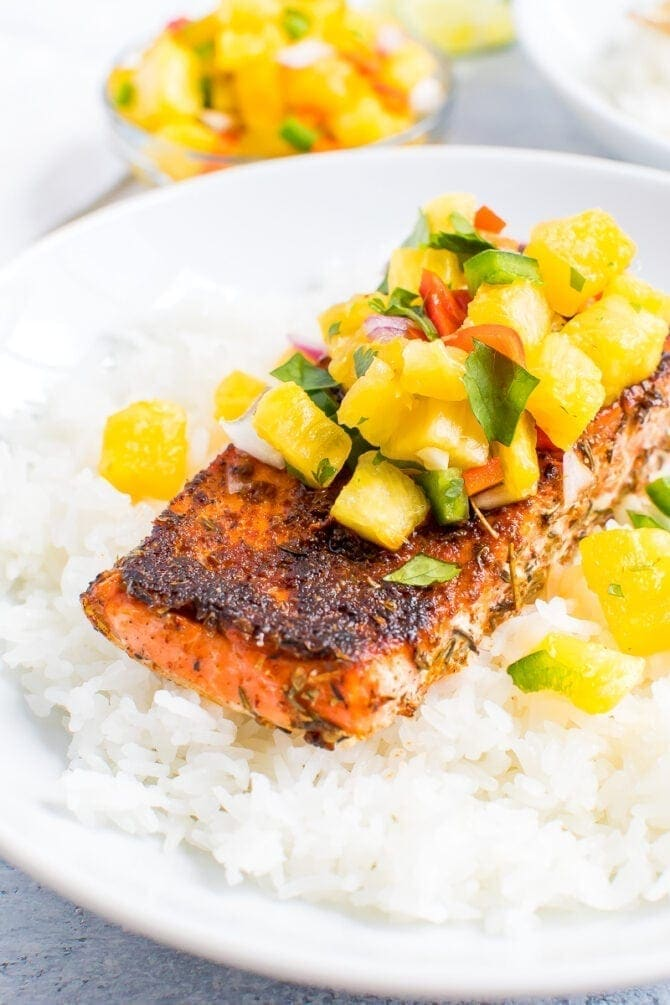 Blacked salmon topped with pineapple salsa and sitting on top of a plate of rice.