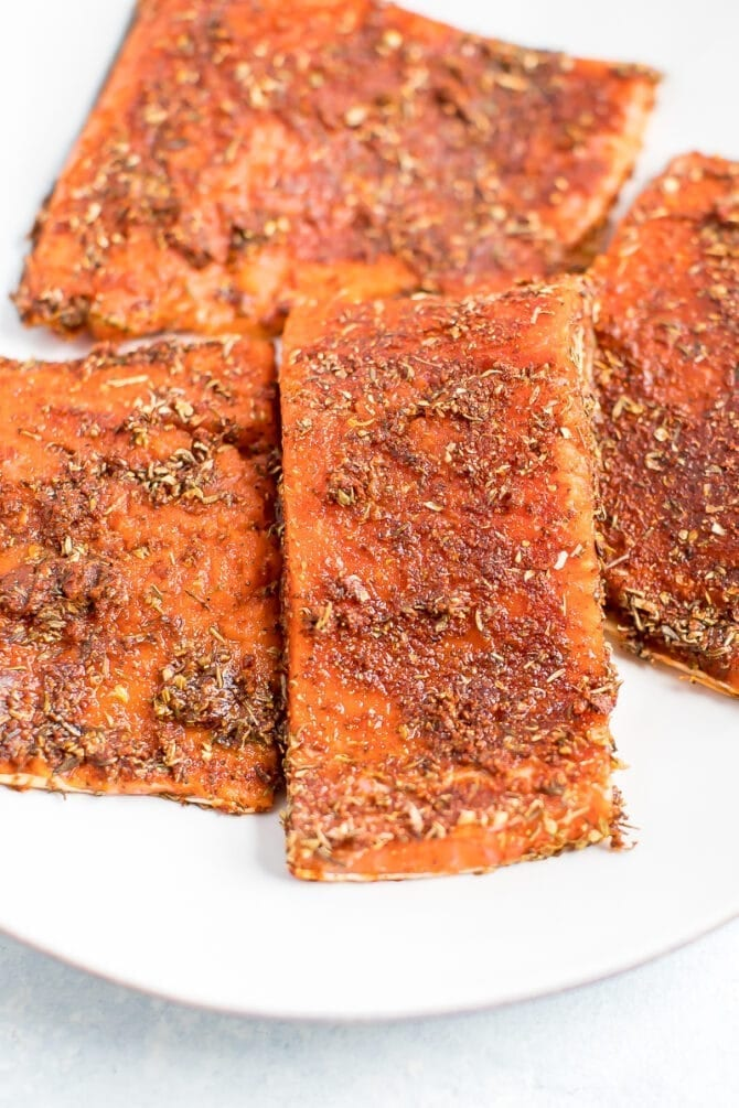 Four pieces of uncooked salmon rubbed with blacked seasoning.